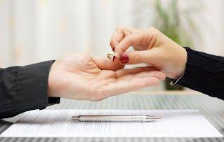 Ženska ruka predaje prsten uz papire za razvod